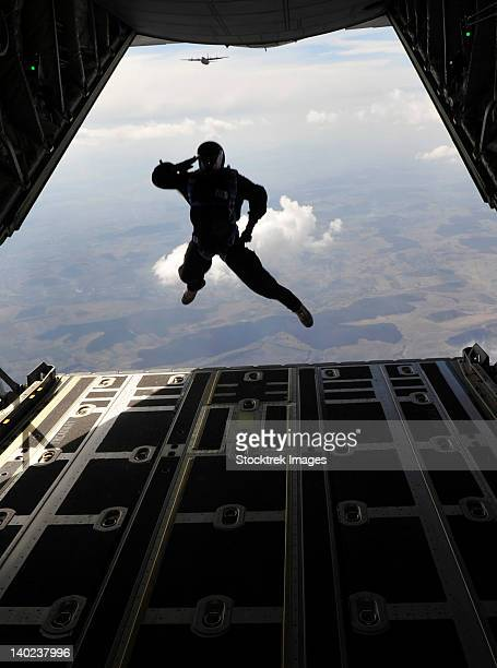 A paratrooper salutes as he jumps out of a C-130J Super Hercules.