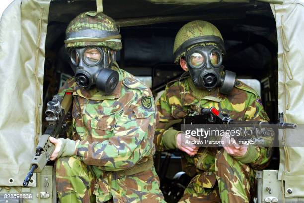 Paratroopers Private Charlie Curnow holding a SA80A2 with Private Neil Clish holding a GPMG from 3rd Battalion practice wearing gas masks near their...