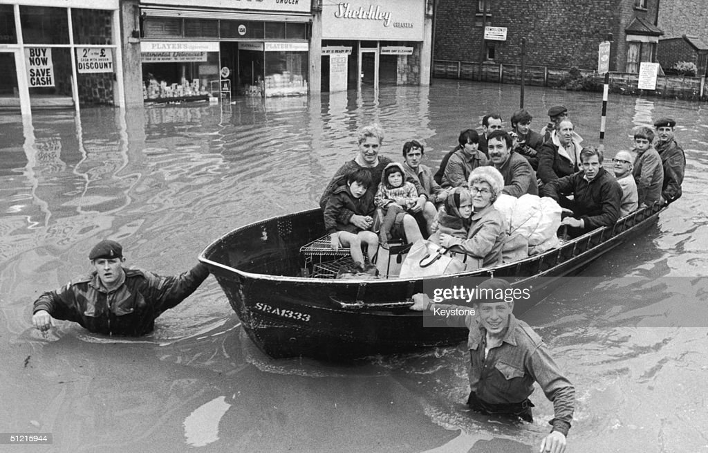 Paratroopers towing people to safety along Walton Road, East Molesey, during an operation to rescue victims of the flood in Surrey, 18th September 1968.