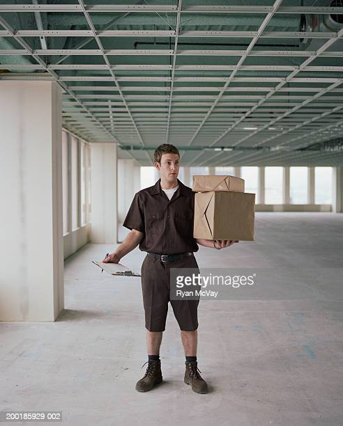 Parcel delivery man in empty office space