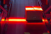 A parcel is illuminated by a red sensor light beam as it passes through a scanning machine at a mechanized postal delivery base operated by DHL a...