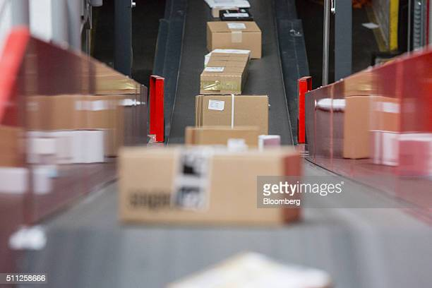 Parcels and boxes move along a conveyor at a mechanized postal delivery base operated by DHL a unit of Deutsche Post AG in Darmstadt Germany on...