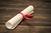 A parchment diploma scroll, rolled up with red ribbon on wooden backgroung