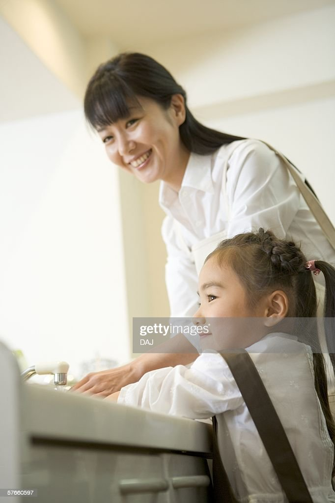Parent and child are washing hands together : Stock Photo