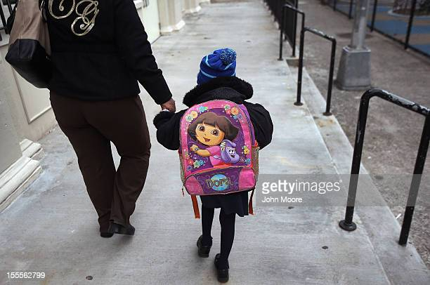 A parent and child arrive to school on November 5 2012 in the East Village neighborhood of New York United States Students at Public School 188 like...