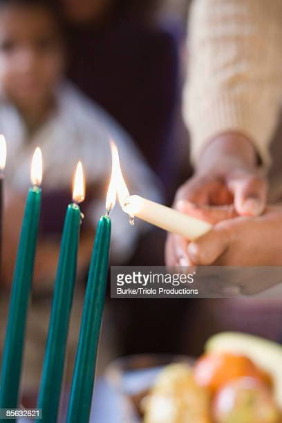 Parent and child lighting Kwanzaa candles