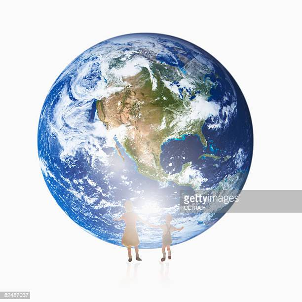 Parent and child stand in front of the earth.