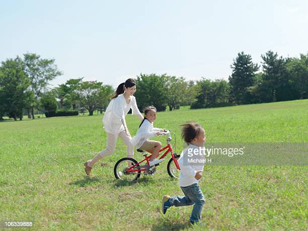 Parent and child who plays with bicycle in park