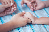Parent and children holding hands and praying together on blue wooden table