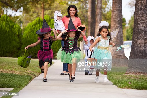 Parent Taking Children Trick Or Treating At Halloween : Stock Photo