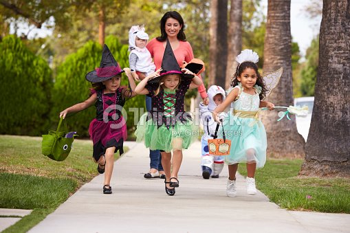 Parent Taking Children Trick Or Treating At Halloween ...