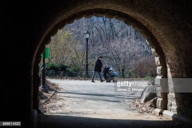 Parent walking pram through central Park seen through archway of over head walk bridge in New York City on Feb 28th 2017