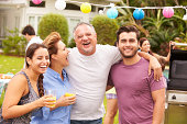 Parent With Adult Children Enjoying Party In Garden With Drinks Laughing And Smiling