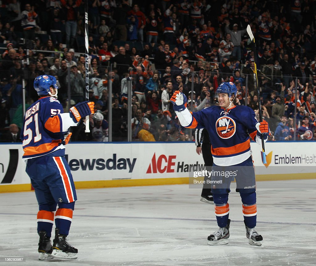 P.A. Parenteau (R) #15 of the News York Islanders scores a powerplay goal at 3:19 of the second period against the Edmonton Oilers and is joined by Frans Nielsen #51 (L) at the Nassau Veterans Memorial Coliseum on December 31, 2011 in Uniondale, New York.
