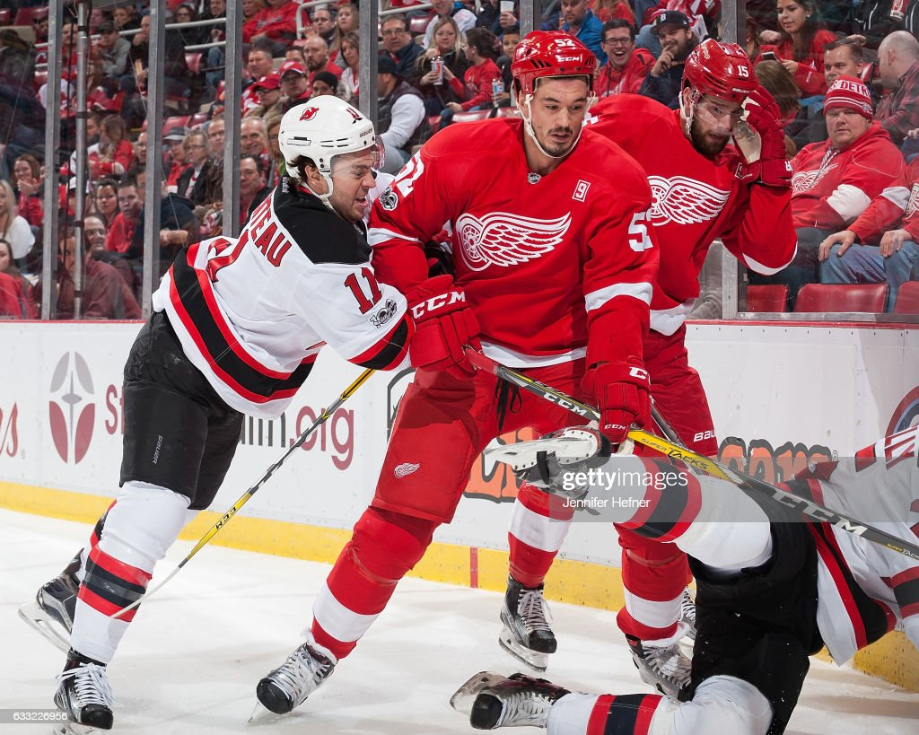 P.A. Parenteau #11 of the New Jersey Devils battles along the boards with Jonathan Ericsson #52 of the Detroit Red Wings during an NHL game at Joe Louis Arena on January 31, 2017 in Detroit, Michigan.
