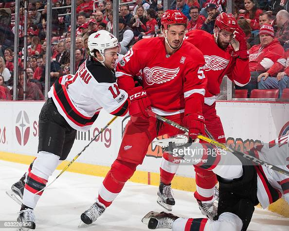 A Parenteau of the New Jersey Devils battles along the boards with Jonathan Ericsson of the Detroit Red Wings during an NHL game at Joe Louis Arena...
