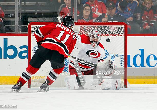 Parenteau of the New Jersey Devils shoots the puck past goalie Cam Ward of the Carolina Hurricanes for a goal in the shootout of their game at the...