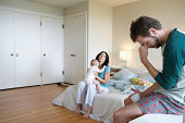 Parents and baby girl (9-12 months) in bedroom, man holding head