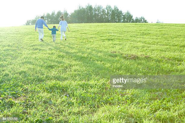 Parents and boy holding hands and walking on field