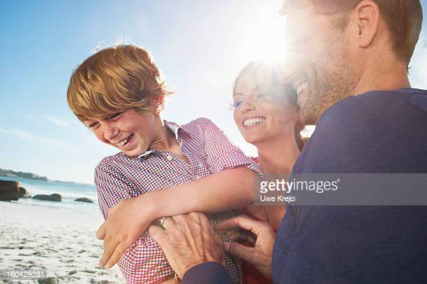 Parents and Boy (6-8) playing outdoors