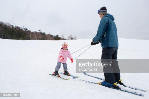 Los padres y niños disfrutando de esquí : Foto de stock