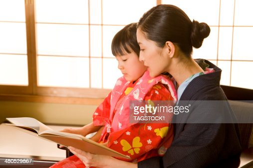 Parents and child in yukata reading book : Stock Photo