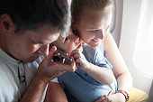 Mother father and little son in the airplane. The have handsfree talking on the cell or listening something