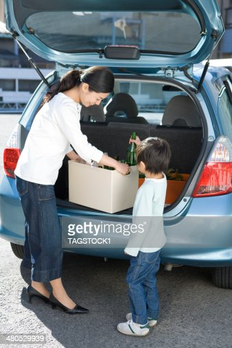 Parents et enfants sur voiture de bouteilles vides de chargement : Photo
