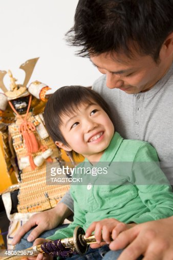 Parents and child sitting in front of May doll : Stock Photo