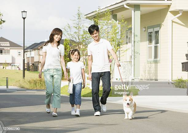 Parents and child walking their dog