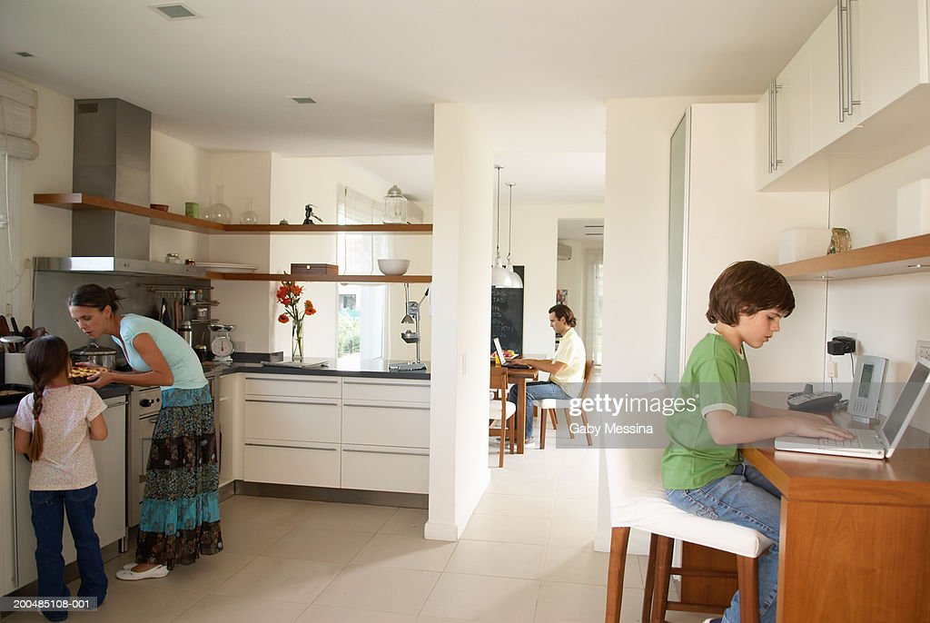 Parents and children (7-11) at home, boy and father using laptops : Stock Photo