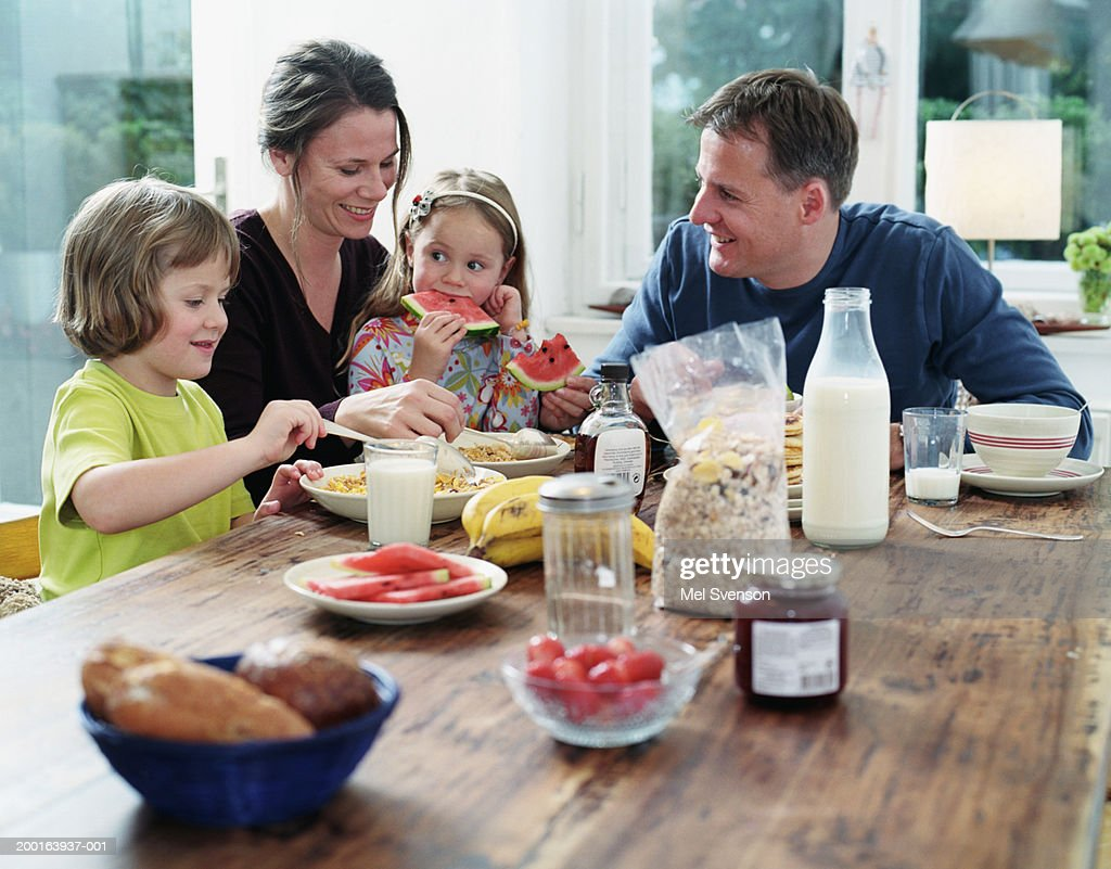 Parents and children (4-6) at table having breakfast : Stock Photo