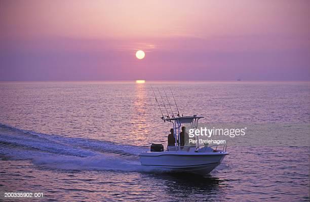 Parents and children cruising on pleasure boat, sunset