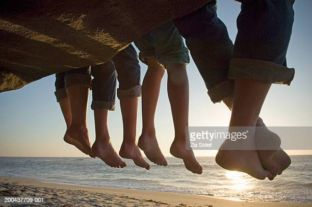 Parents and children dangling feet from ledge above beach, low section, sunset