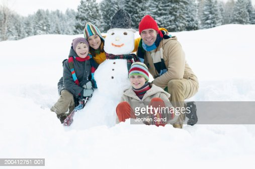 Parents and children (9-13) either side of snowman, smiling, portrait