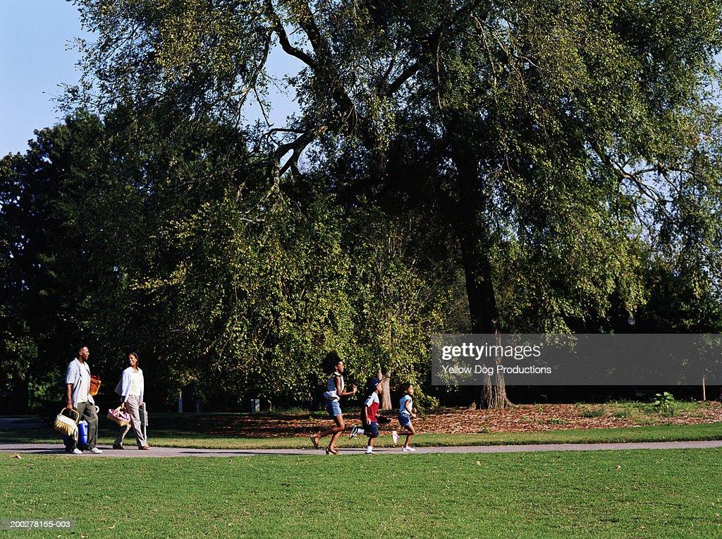 Parents and children (5-13) entering park, parents with picnic gear