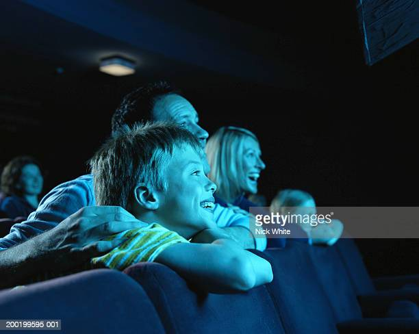 Parents and children (8-10) in cinema, laughing, side view