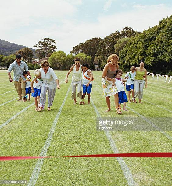 Parents and children (4-9) in three legged race at school sports day