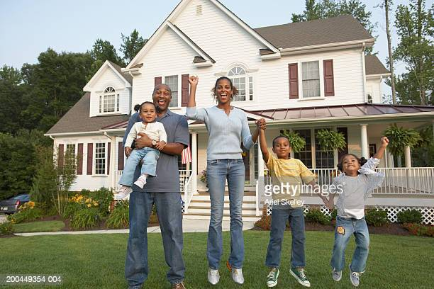 Parents and children (18 months to 7) jumping in front of home