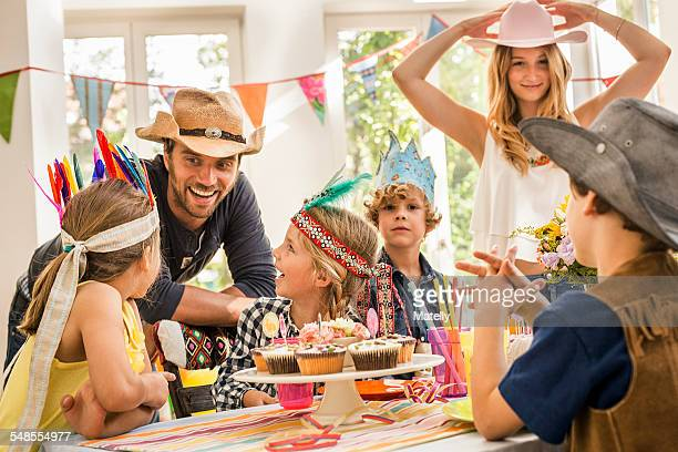 Parents and children laughing and chatting at kids birthday party
