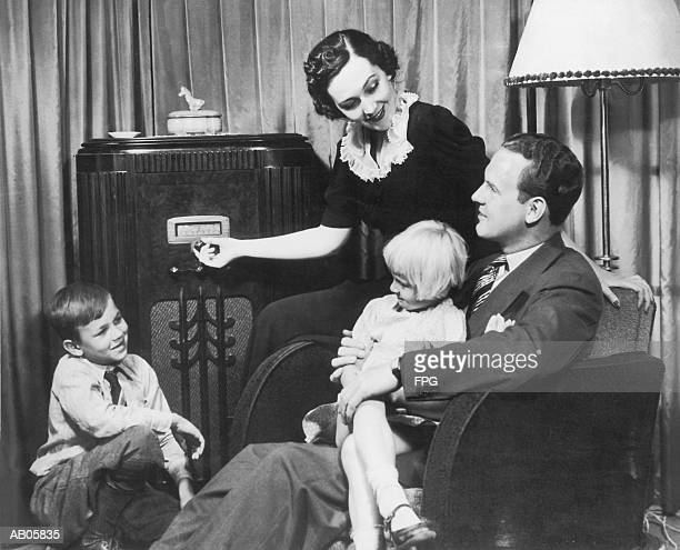 Parents and children (4-10) listening to radio set (B&W)