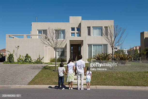 Parents and children (7-11) looking at new home, rear view