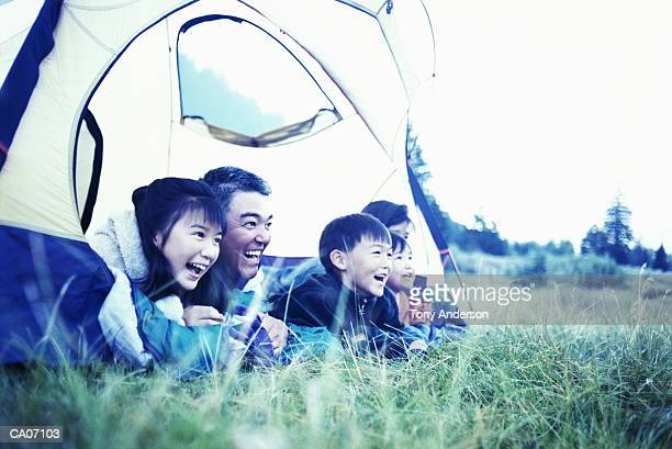 Parents and children (5-11) lying on sleeping bags in tent, laughing