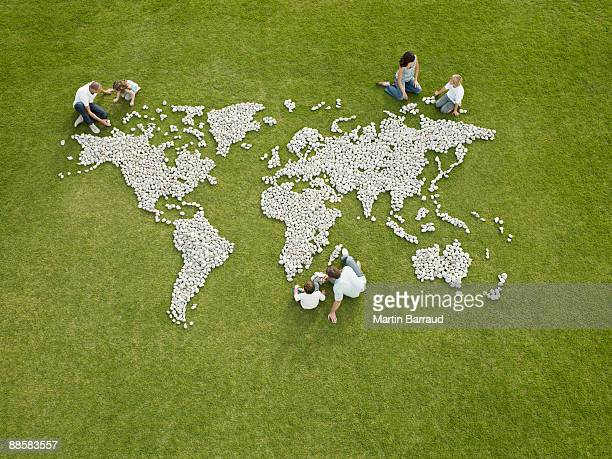 Parents and children making world map made of rocks