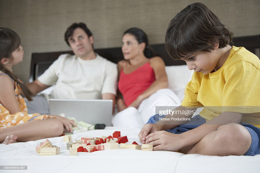 Parents and children (4-10) on bed, boy playing with toys : Stock Photo