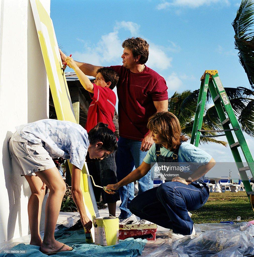 Parents and children (9-14) painting door, side view : Stock Photo