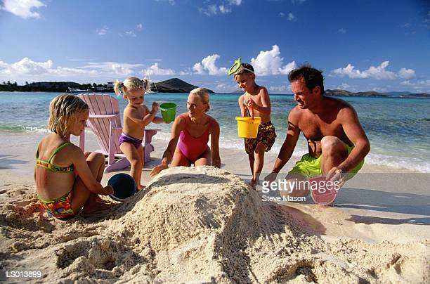 Parents and children (2-6) playing in sand at beach