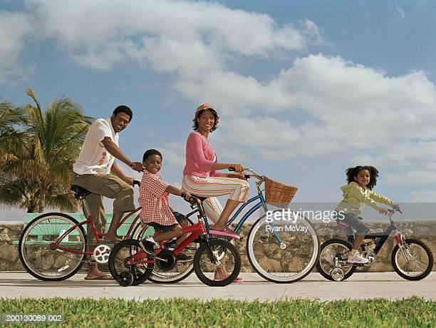 Parents and children (4-6) riding bicycles, portrait