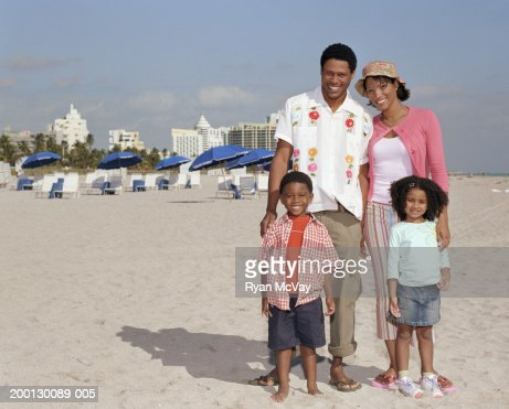 Parents and children (4-6) smiling on beach, portrait