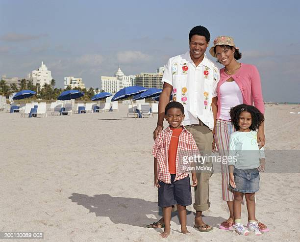Parents and children (4-6) smiling on beach, portrait
